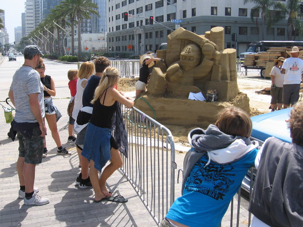 People at the foot of Broadway Pier pause to watch three sand sculptures being created for the 2017 U.S. Sand Sculpting Challenge this Labor Day weekend.