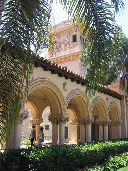 People walk past ornate arches connecting the Casa de Balboa and the House of Hospitality.