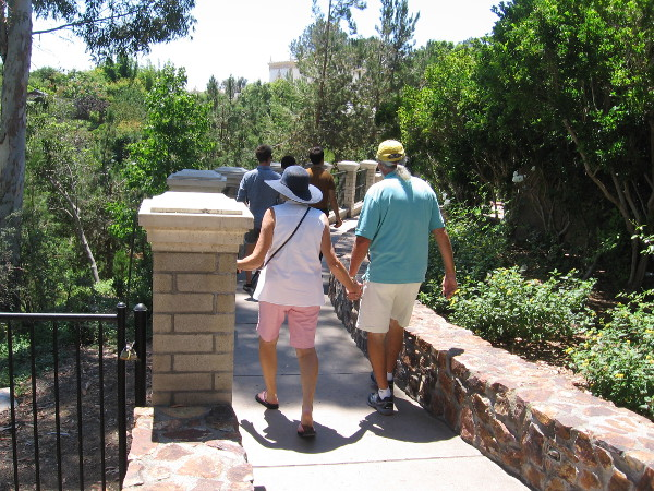 Folks walk down toward the Casa del Rey Moro Garden.