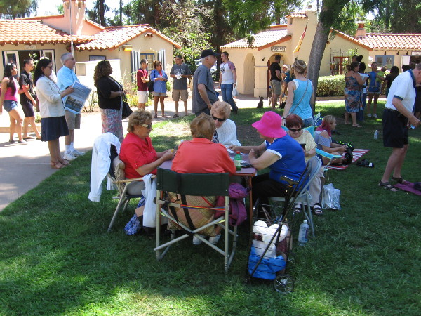 Ladies play cards on the grass at the House of Pacific Relations International Cottages.
