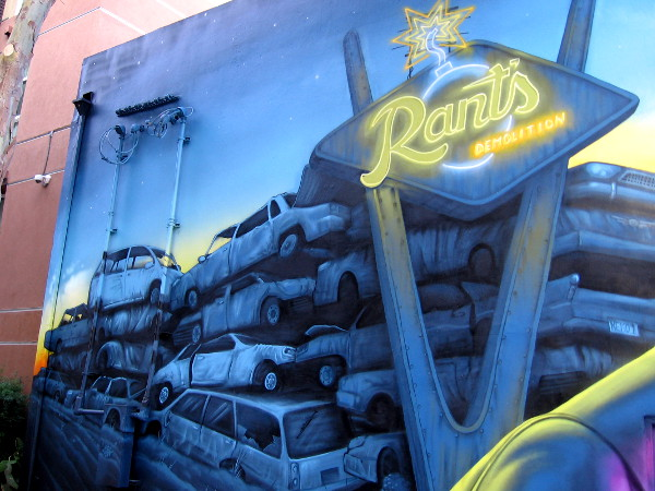 Lots of old wrecked cars are piled up behind Rant's Demolition neon sign!