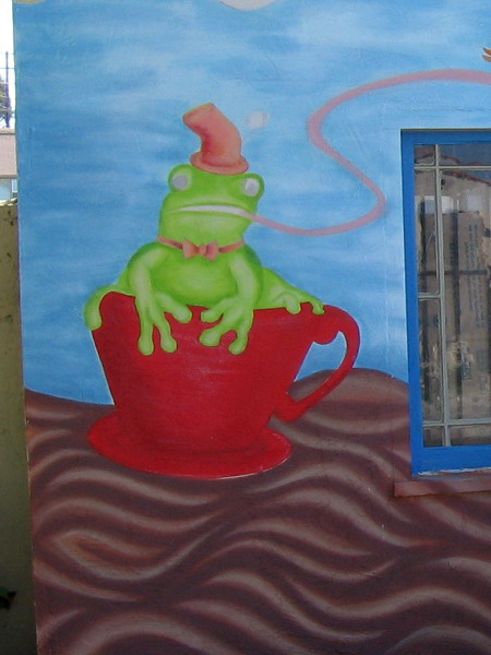 A frog in a red teacup floats on a tea river.