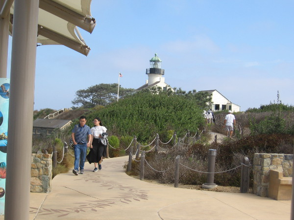 South of the lighthouse, people walk toward the gray whale migration overlook.