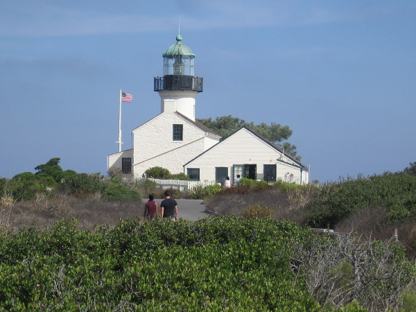 People approach the handsome lighthouse from the south.