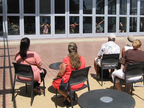Outside the library, in the courtyard, the audience now watches dancers framed in glass windows!