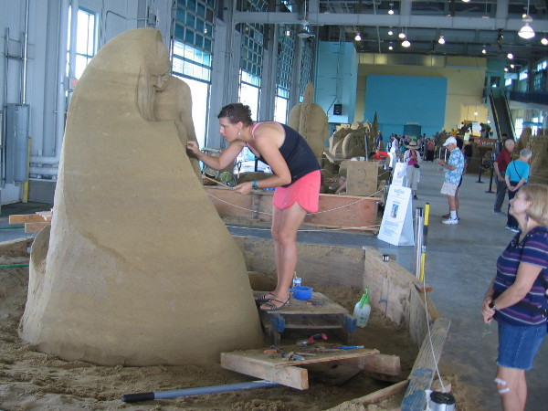 Susanne Ruseler, sand artist from the Netherlands, works on a fine sculpture that juxtaposes youth and old age.