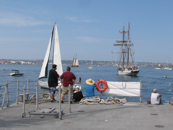 People watch as the Irving Johnson heads out to face the Spirit of Dana Point in a cannon battle on San Diego Bay.