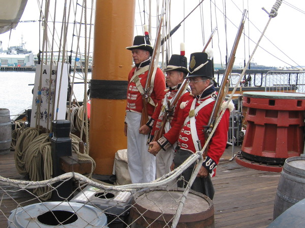 The three Royal Marines stand at attention on the main deck of HMS Surprise.