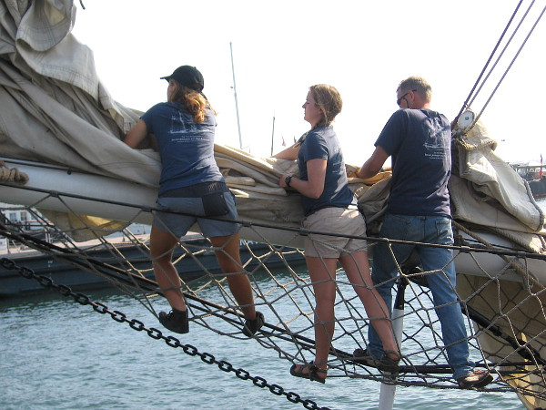 Several of Exy Johnson's hardworking crew wrestle a jib sail onto the bowsprit.