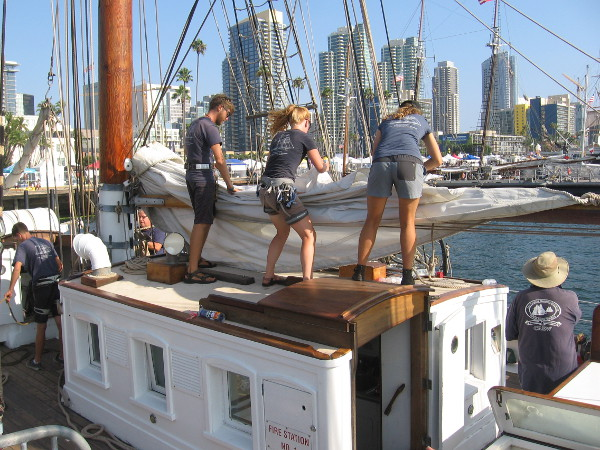 Teamwork is required as a staysail is neatly furled.