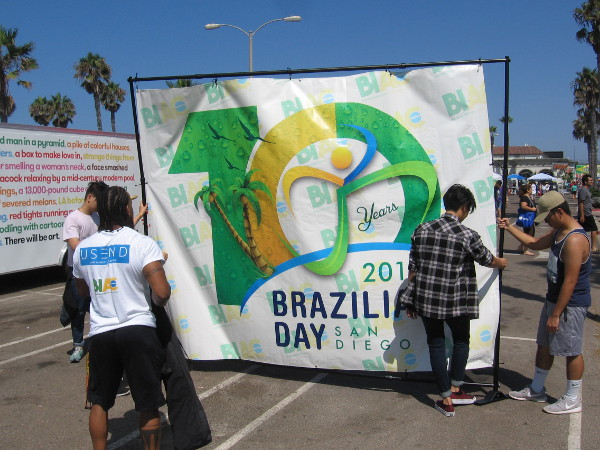 People hang a banner as the San Diego Brazilian Day Festival gets started late in the morning.
