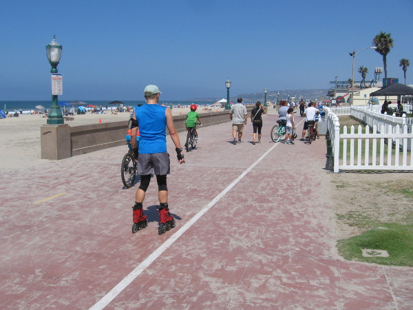 Nearby, on the Mission Beach boardwalk, people are walking, biking and skating by the beautiful blue ocean.