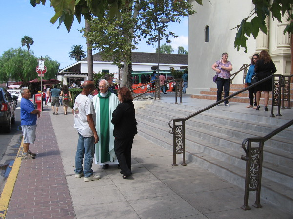 Priest of the Immaculate Conception Catholic Church in Old Town talks to people in front of the historic church after Sunday Mass.