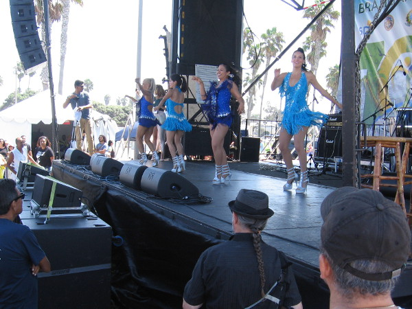 Smiling ladies commenced an energetic dance routine on the stage to the delight of the growing crowd.