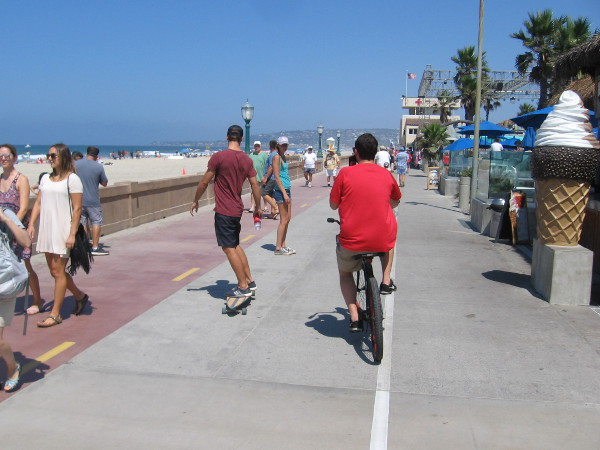 People head down the fun, always busy Mission Beach boardwalk, not far from public art titled Green Flash.