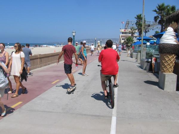 People head down the fun, always busy Mission Beach boardwalk, not far from public art titled Green Flash.