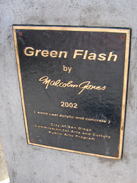 A plaque describes the unusual public artwork. Green Flash by Malcolm Jones, 2002. Solid cast acrylic and concrete.
