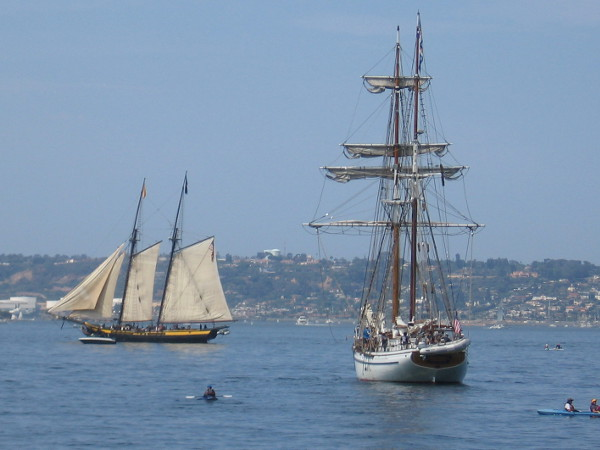 Two beautiful tall ships maneuver on blue San Diego Bay.