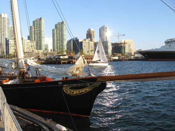 A sailboat glides between beautiful yacht America docked at the Maritime Museum of San Diego and the shining downtown skyline.