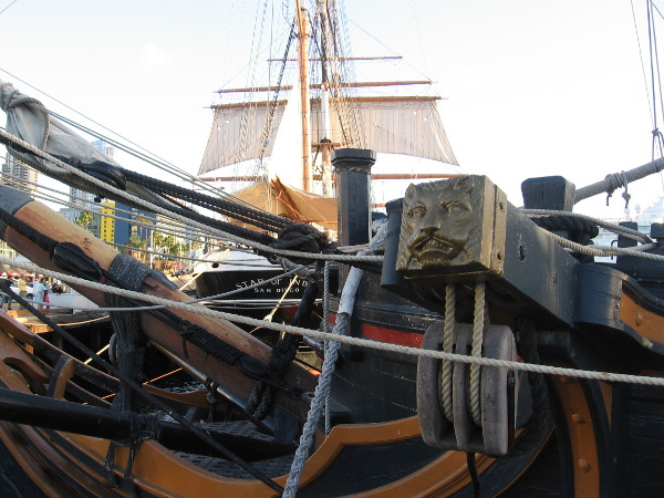 The sails of Star of India rise beyond one cathead of HMS Surprise.