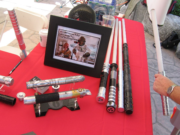 Someone picks up one of the cool lightsabers on display.