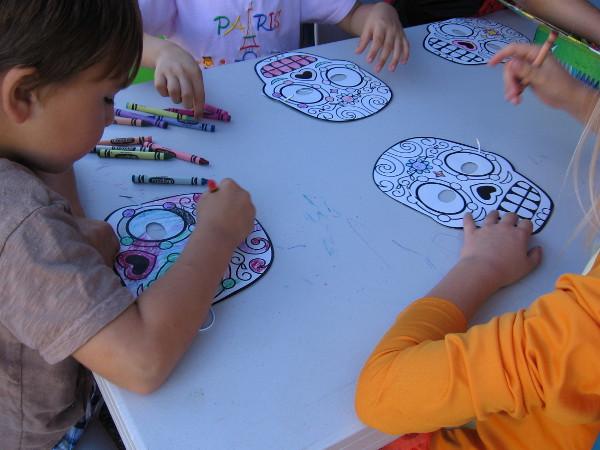 Kids at Halloween Family Day in Balboa Park color Dia de los Muertos skulls.