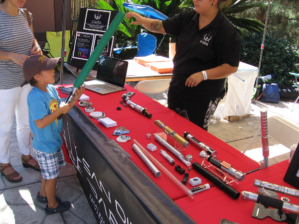 A kid checks out one of the cool lightsabers. As you might have noticed, I took these photos on two different days during Maker Faire San Diego.