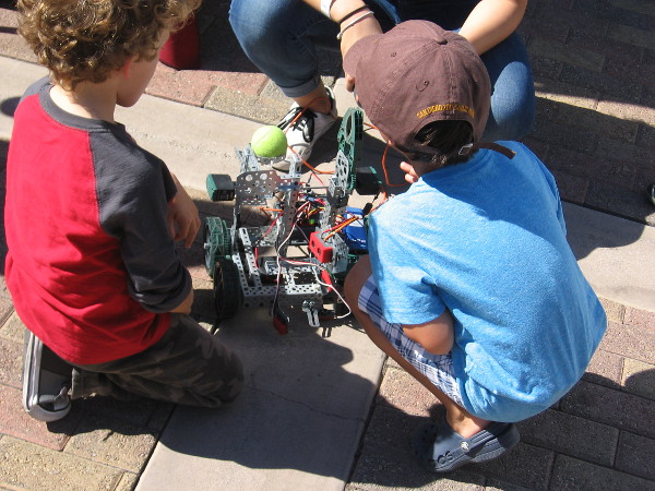 Kids check out another robot in the garden.