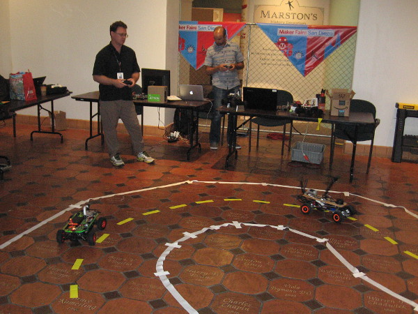Small autonomous cars on a track inside the San Diego History Center. They were being controlled remotely in order to gather navigational data.