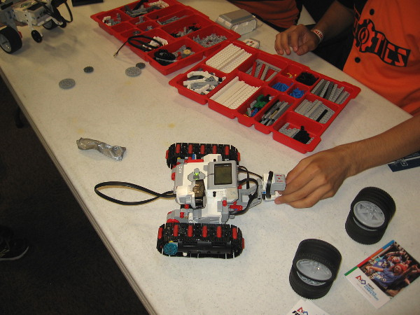 A student participating in the First Robotics Competition demonstrates a small vehicle that they built. Many robots can be seen up close in the San Diego History Center.