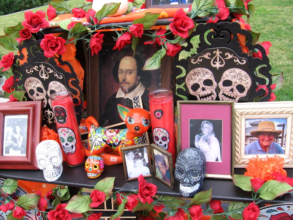 Day of the Dead altar created by the Old Globe Theatre contains photos of departed loved ones, roses, candles, and an image of Shakespeare.
