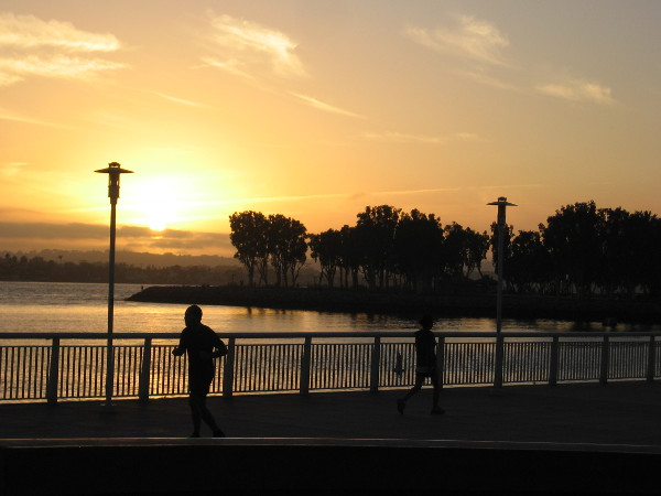 People jog along San Diego's Embarcadero as evening approaches.