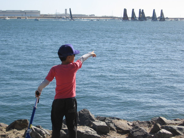 Boy points toward fleet of high-tech foil-equipped catamarans manned by elite level teams. Another wild race is about to begin.