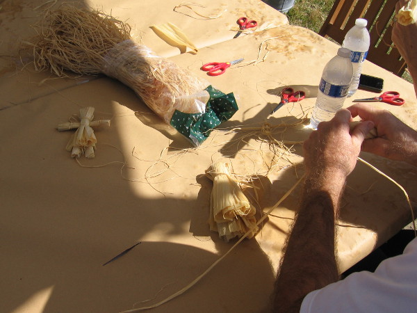 Folks young and old were trying their hand at making corn husk dolls.