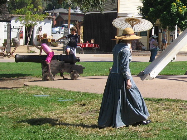 Lady with old-fashioned parasol walks through Old Town San Diego State Historic Park's Plaza de las Armas.