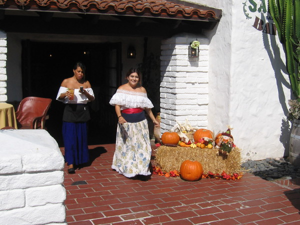 A smiling señorita walks near some pumpkins.
