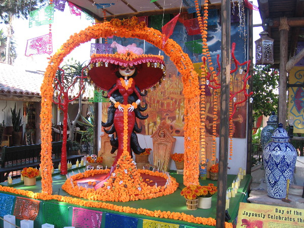 An elaborate Día de los Muertos decoration standing beside the Fiesta de Reyes stage is bright with autumn colors.