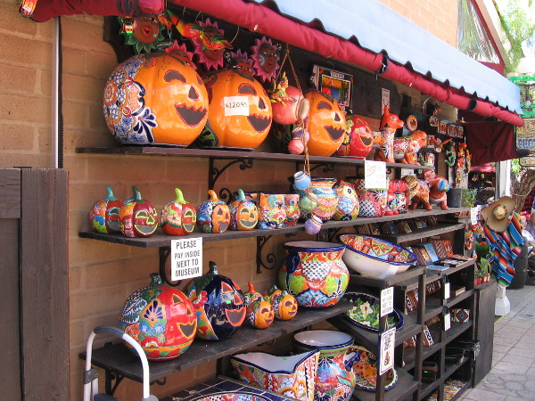 Ceramic pumpkins line shelves at an outdoor Old Town marketplace.