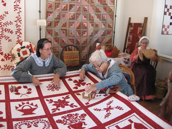 Ladies work on a quilt inside the Threads of the Past Living History Activity Center.