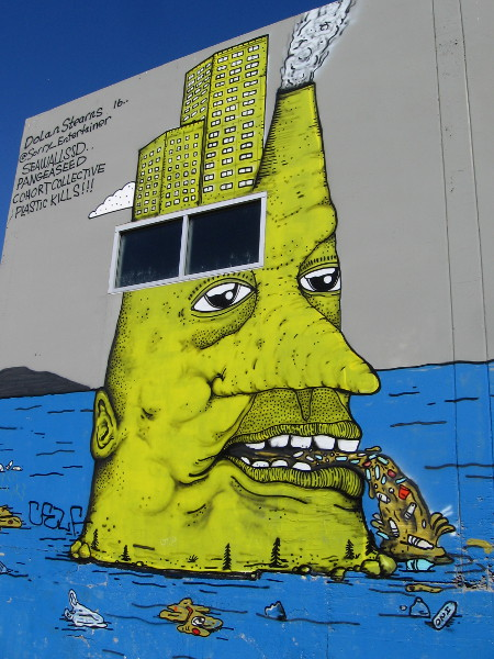 The yellow human head, topped by city buildings and a smokestack, vomits disgusting trash into the blue ocean.