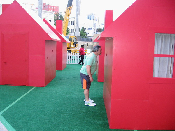 Someone in downtown San Diego peers through a spy hole into a tiny red house in Horton Plaza Park.
