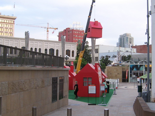 Several plain red houses stand in Horton Plaza Park--and one is dangling high in the sky from a crane!