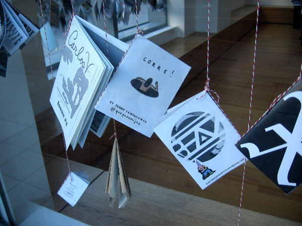 A bunch of creative zines hang inside the windows of the downtown Museum of Contemporary Art San Diego, in their gallery at America Plaza.