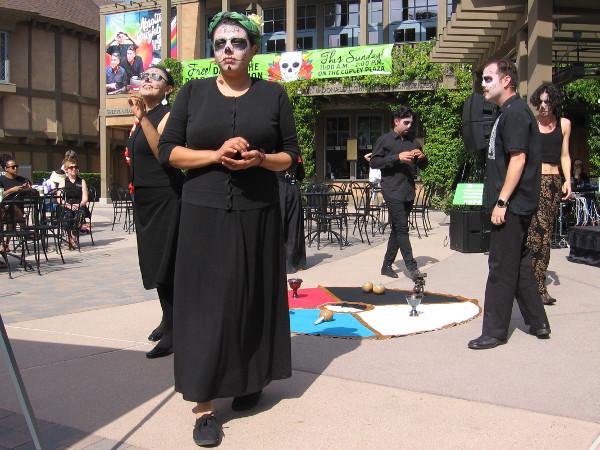 A performance of La Muerte Descansa en Paz (Death Rests in Peace) begins. The dead enter in front of a living audience.