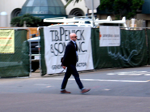 Someone walks briskly to work in downtown San Diego.