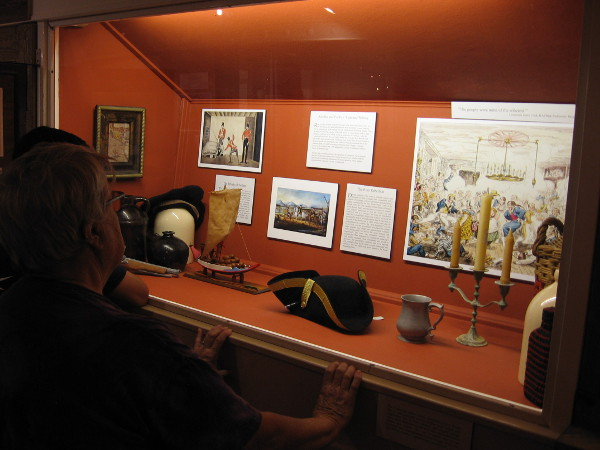 Visitors to the Maritime Museum of San Diego view a display concerning the history of rum.