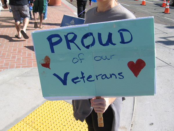 Someone hold a sign that reads Proud Of Our Veterans.