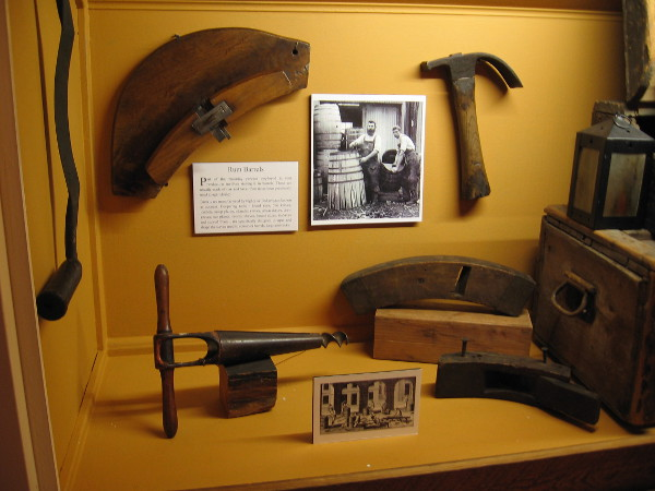 A display in the Gould Eddy Gallery shows some of the coopering tools used in making oak rum barrels.