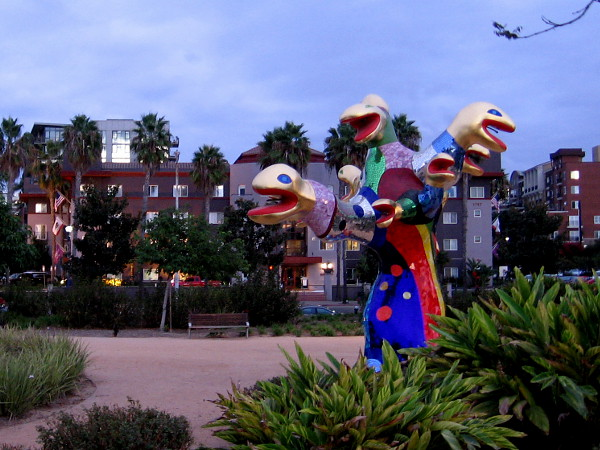 To the east, nearby building windows and Niki de Saint Phalle's colorful Serpent Tree gleam, reflecting late light.