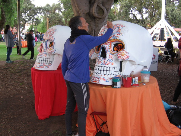 An artist paints two large skulls--calaveras--in Old Town's Plaza de las Armas during Dia de los Muertos.